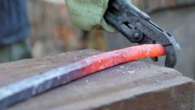 O ferreiro trabalha o metal Artesão, escocês na forja privada na vila Sopros do malho no metal quente vídeos de arquivo