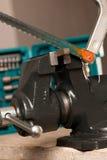 O ferro do corte com viu na ferramenta vice, dispositivo de aperto Imagem de Stock