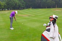 O ferro do jogador de golfe disparou em um fairway da paridade 4. Imagem de Stock Royalty Free