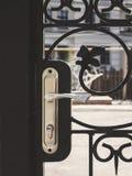 O ferro forjado cinzelou a porta da rua com um puxador da porta Close-up Imagens de Stock Royalty Free