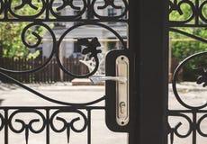 O ferro forjado cinzelou a porta da rua com um puxador da porta Close-up Fotografia de Stock Royalty Free
