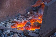 o ferro original feito a mão do metal quente aumentou na fornalha da forja Imagem de Stock Royalty Free