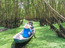 O ferryman toma o viajante em uma excursão do barco ao longo dos canais na floresta dos manguezais imagens de stock