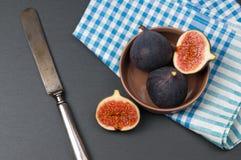 O figo cortado frutifica na bacia cerâmica na pedra preta Fotografia de Stock