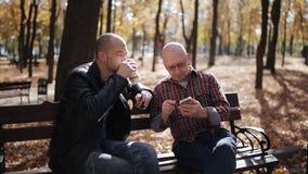 O filho adulto de um pai idoso ensina o smartphone no parque do outono em um banco vídeos de arquivo