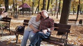 O filho adulto toma imagens de pais idosos no smartphone que senta-se no banco no parque do outono vídeos de arquivo