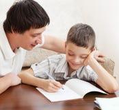 O filho de ajuda do pai faz trabalhos de casa Fotografia de Stock