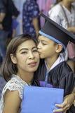 O filho do retrato graduou-se do jardim de infância que beija a mãe foto de stock royalty free