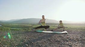 O filho e a mãe felizes estão fazendo exercícios na parte superior da montanha no por do sol Esportes que treinam a mãe e o filho vídeos de arquivo