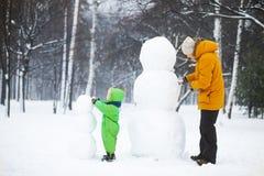 O filho e o pai fazem dois snowmans imagens de stock royalty free
