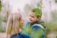 O filho está beijando sua mãe exterior Imagem de Stock