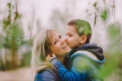 O filho está beijando sua mãe exterior Foto de Stock