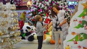O filho está trazendo a seus brinquedos da mãe dois de Santa Claus para escolher no hipermercado durante feriados do Natal Divert filme