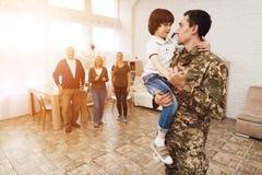 O filho novo encontra um homem na camuflagem em casa imagens de stock royalty free
