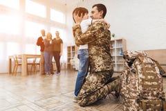 O filho novo encontra um homem na camuflagem em casa foto de stock