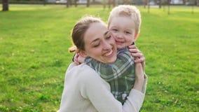 O filho pequeno bonito corre a sua mãe, abraçando e sorrindo no parque no por do sol video estoque