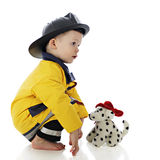 O filhote de cachorro do fogo enfrenta o bombeiro do bebê Fotos de Stock Royalty Free