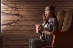 O filme de terror de observação da jovem mulher asiática e come a pipoca com foto de stock royalty free