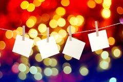 Cartões de papel vazios que penduram em clothespins contra a luz de Natal Foto de Stock