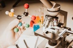 O fim acima da amostra da visão do microscópio com bola do átomo e do modelo molecular da vara para a pesquisa, aprende imagens de stock royalty free
