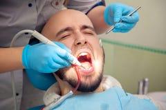 O fim acima da foto do indivíduo considerável trata os dentes da cárie no dental Imagens de Stock