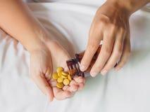 O fim acima da jovem mulher derrama os comprimidos fora da garrafa fotos de stock royalty free