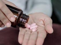 O fim acima da jovem mulher derrama os comprimidos fora da garrafa imagem de stock