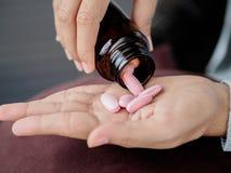 O fim acima da jovem mulher derrama os comprimidos fora da garrafa foto de stock royalty free