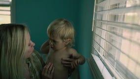 O fim acima da mãe bonita do retrato guarda um filho do bebê, grande janela no fundo Imagens de Stock