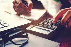 O fim acima da mão da mulher usando a calculadora e escrevendo faz a anotação com Fotos de Stock Royalty Free