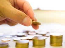 O fim acima da mão do ` s do homem pôs moedas à pilha de moedas Imagem de Stock Royalty Free