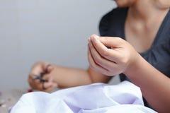 O fim acima da mão da mulher está usando tesouras da costura fotos de stock