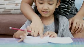 O fim acima da menina asiática do tiro que faz trabalhos de casa e sua mãe ensinam filme