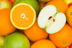 O fim acima da metade cortou laranjas e maçãs Fotos de Stock