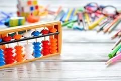 O fim acima da vista do ábaco marca a aritmética mental com o colorido de volta às fontes de escola sobre a tabela branca Espaço  Foto de Stock Royalty Free