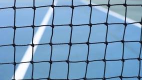 O fim acima das bolas de tênis amarelas bateu a rede em uma corte azul filme