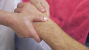 O fim acima das mãos do massagista faz a massagem profissional da mão da mão ao homem adulto filme
