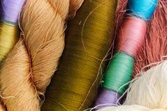 O fim acima de colorido da seda tailandesa crua rosqueia Foto de Stock Royalty Free