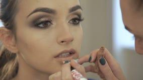 O fim acima de compensa pela mulher bonita, aplicando o lápis do batom video estoque