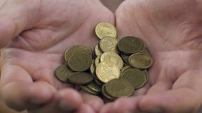 O fim acima de equipa as mãos colocadas que mostram euro- moedas, rendimentos reduzidos e conceito da pobreza filme