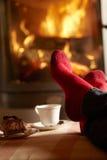 O fim acima de equipa os pés que relaxam pelo incêndio de registro Cosy foto de stock royalty free