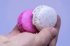 O fim acima de macarons cor-de-rosa e brancos em uma mão do ` s Fotografia de Stock