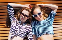O fim acima de um retrato do verão do estilo de vida de dois amigos de meninas relaxado e que obtêm toma sol, colocando na praia, Imagem de Stock