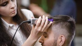 O fim acima do barbeiro fêmea profissional vestido na roupa ocasional está servindo o cliente na utilização do barbeiro moderna filme