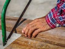 O fim acima do carpinteiro que vê uma placa com uma madeira da mão considerou Profe fotografia de stock
