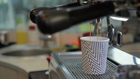 O fim acima do coffe está sendo derramado ao copo da máquina e levado embora pela mão masculina filme