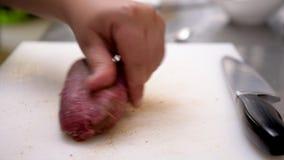 O fim acima do cozinheiro masculino entrega o tempero de uma parte de carne crua da carne video estoque