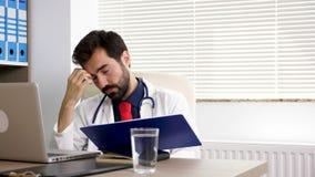 O fim acima do doutor no pensamento do escritório e no seu assistente está trazendo os resultados do laboratório vídeos de arquivo