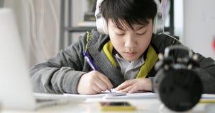 O fim acima do estudante adolescente novo escuta a música e fazer trabalhos de casa em casa, movimento da zorra esquerda para a d video estoque
