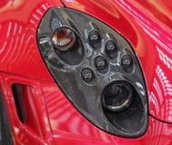 O fim acima do farol dianteiro direito do esporte luxuoso vermelho Ca Imagens de Stock